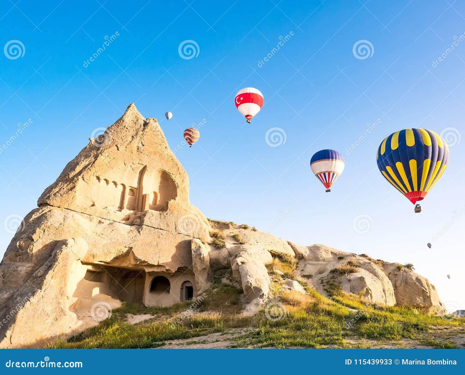 五颜六色的热空气迅速增加飞行在岩石风景在Cappadoc