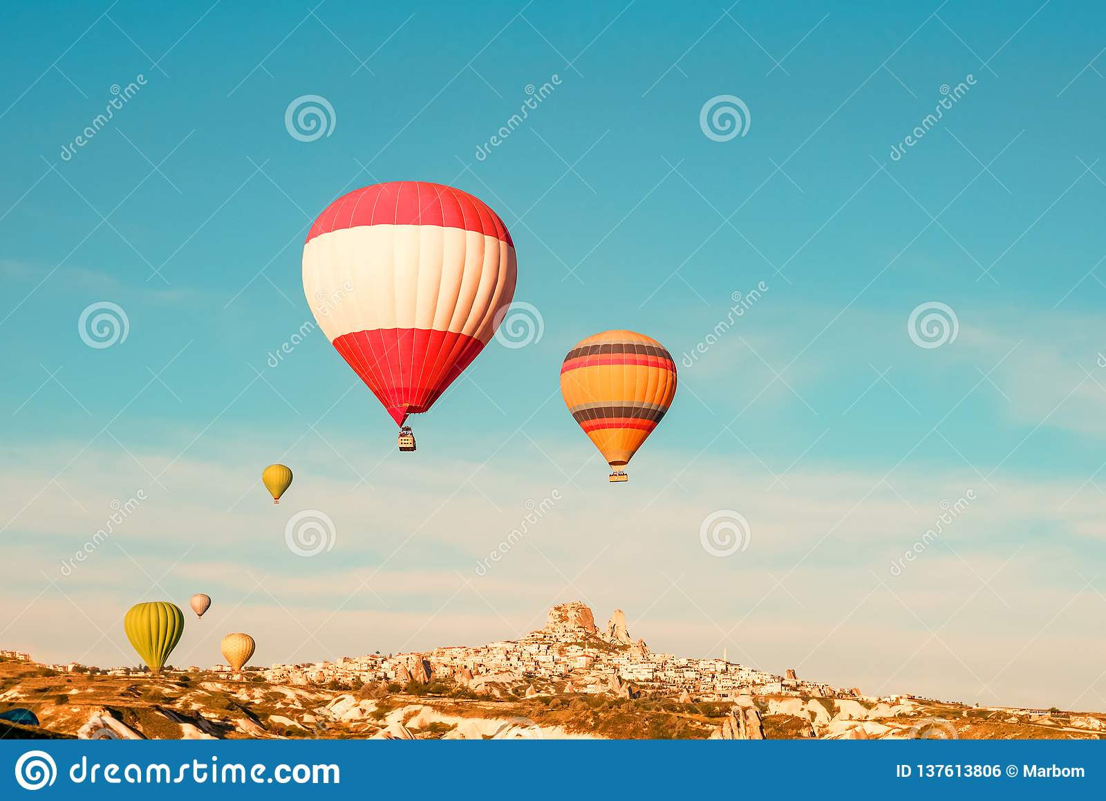 五颜六色的热空气迅速增加飞行靠近Uchisar城堡在日出,卡帕多细亚,土耳其