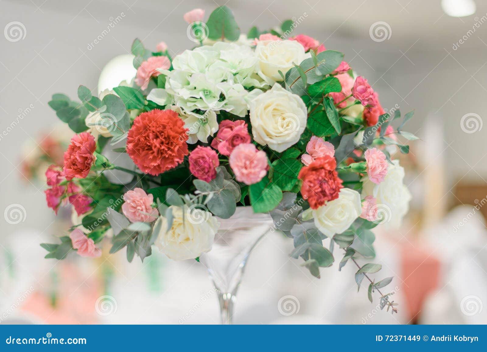 五颜六色的玫瑰豪华花束在一个现代花瓶的在被弄脏的背景