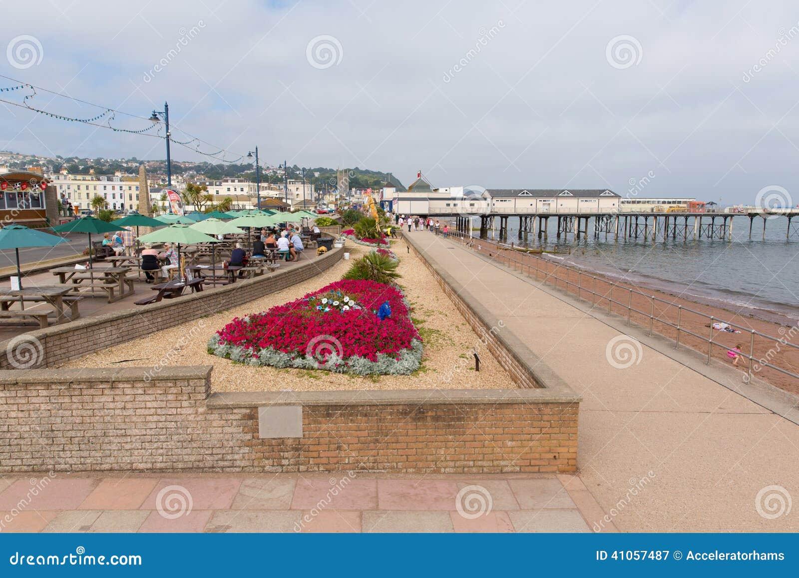 五颜六色的花和假日游客Teignmouth码头和海滩德文郡英国英国