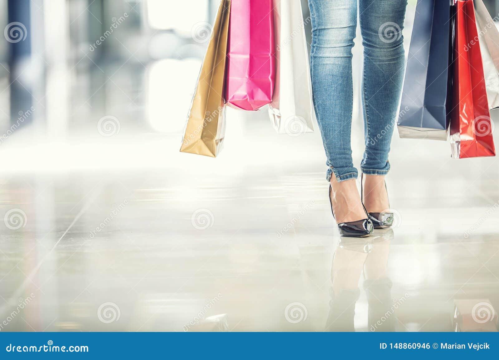 五颜六色的购物带来在顾客妇女的手上和她的腿牛仔裤和鞋子