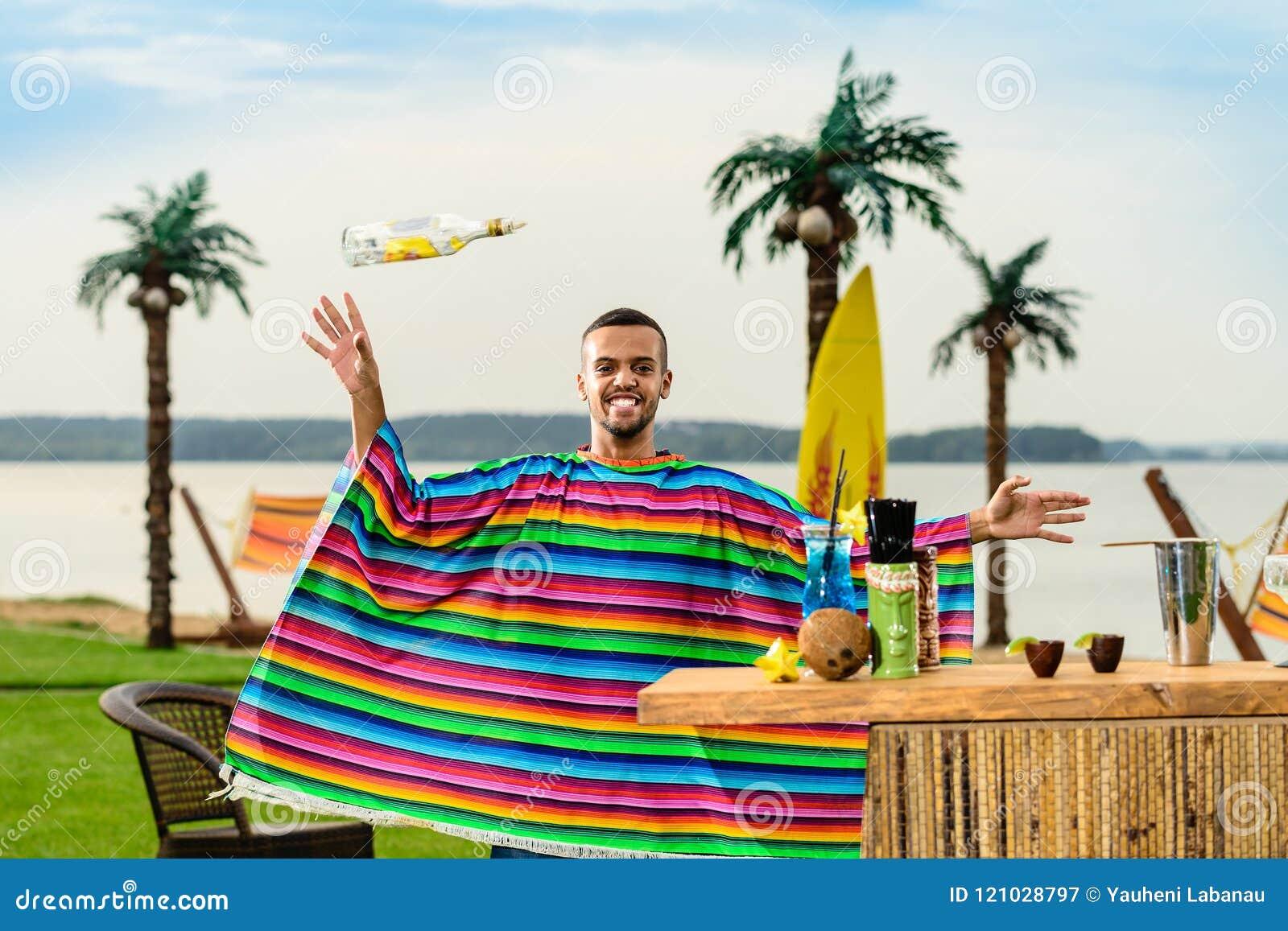 五颜六色的雨披的英俊的正面墨西哥侍酒者投掷