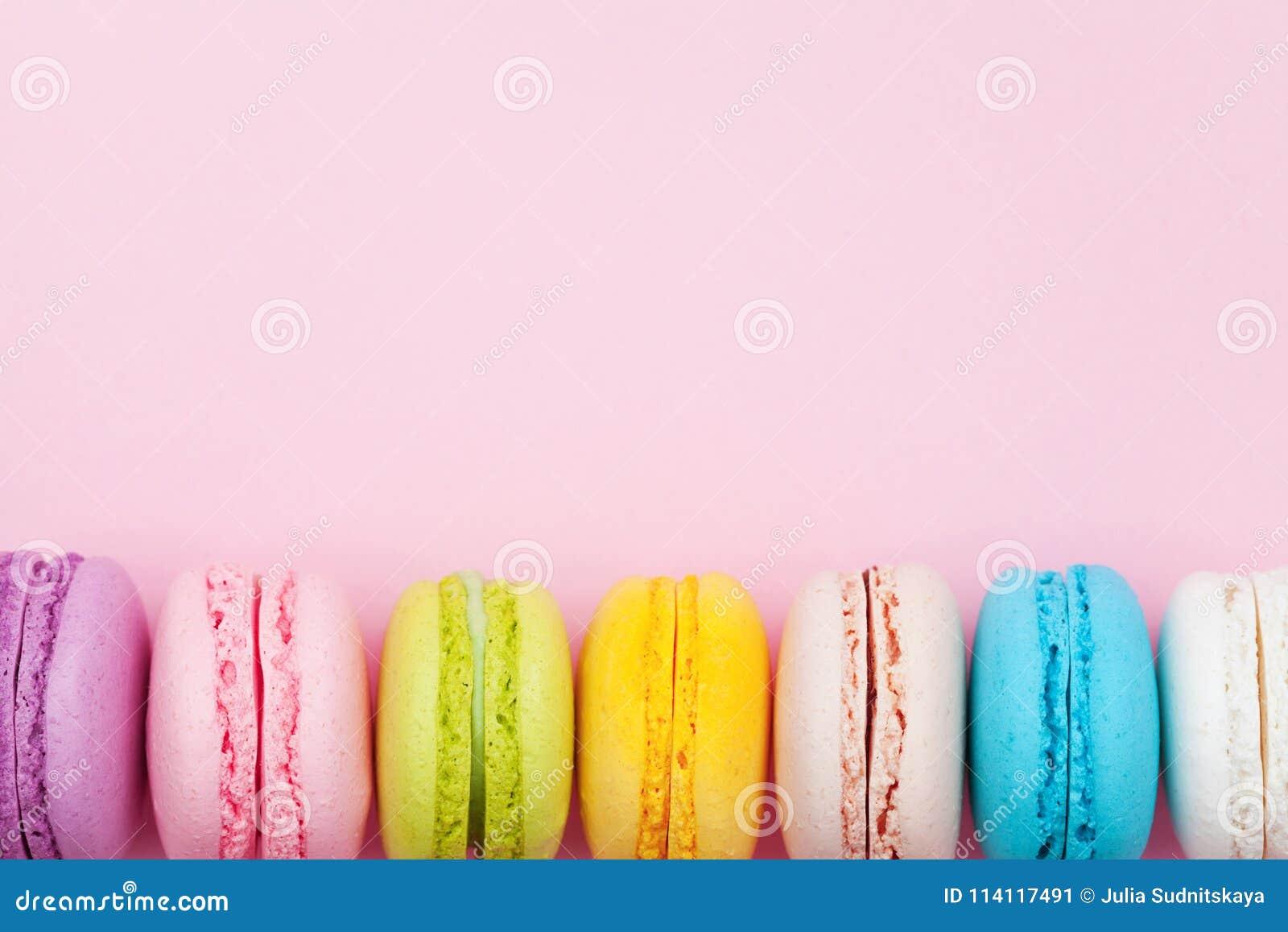 五颜六色的macaron或蛋白杏仁饼干在桃红色淡色背景顶视图 平的位置构成