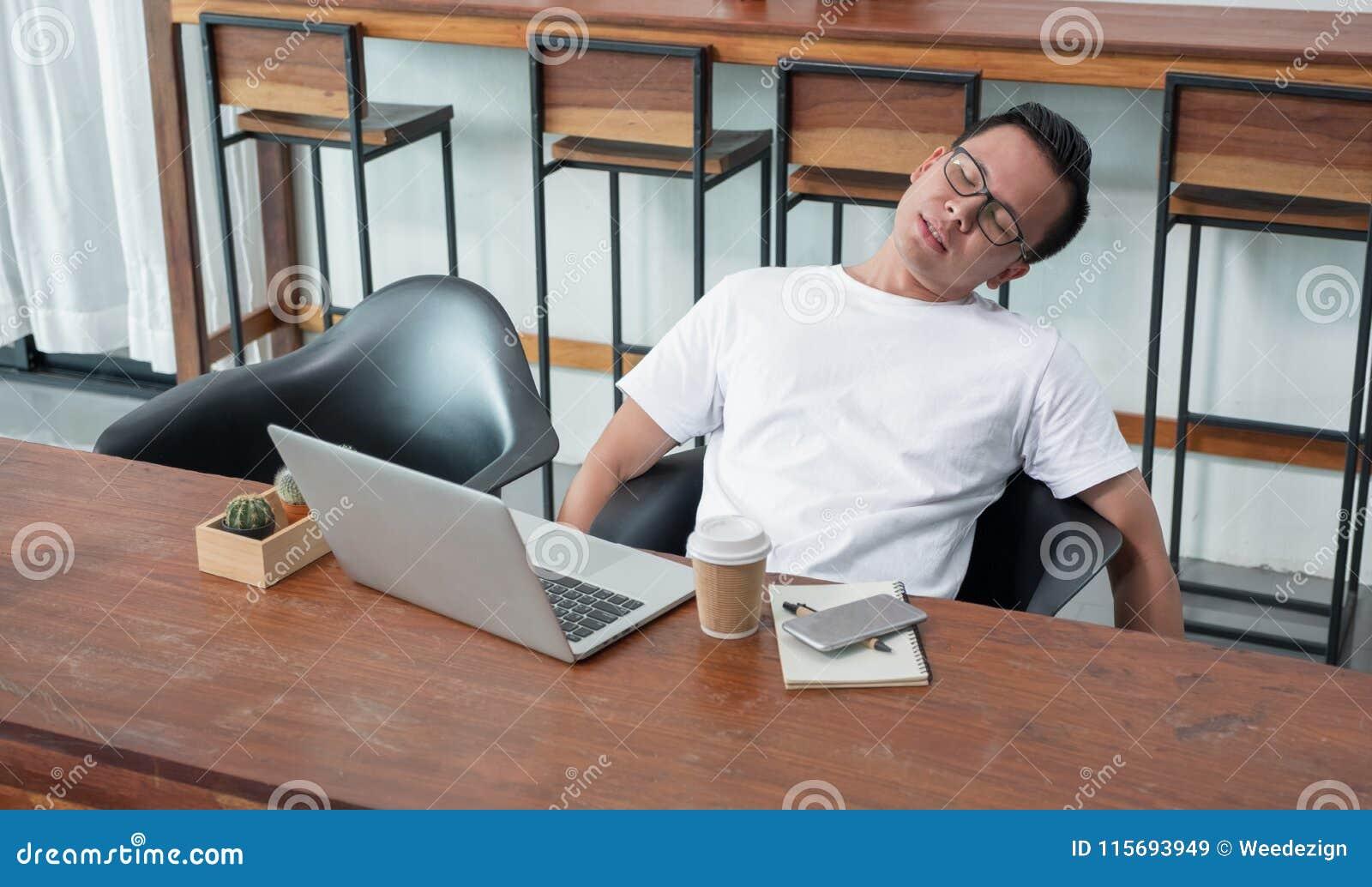 亚洲偶然人松劲从工作疲倦的感觉在coffe的膝上型计算机