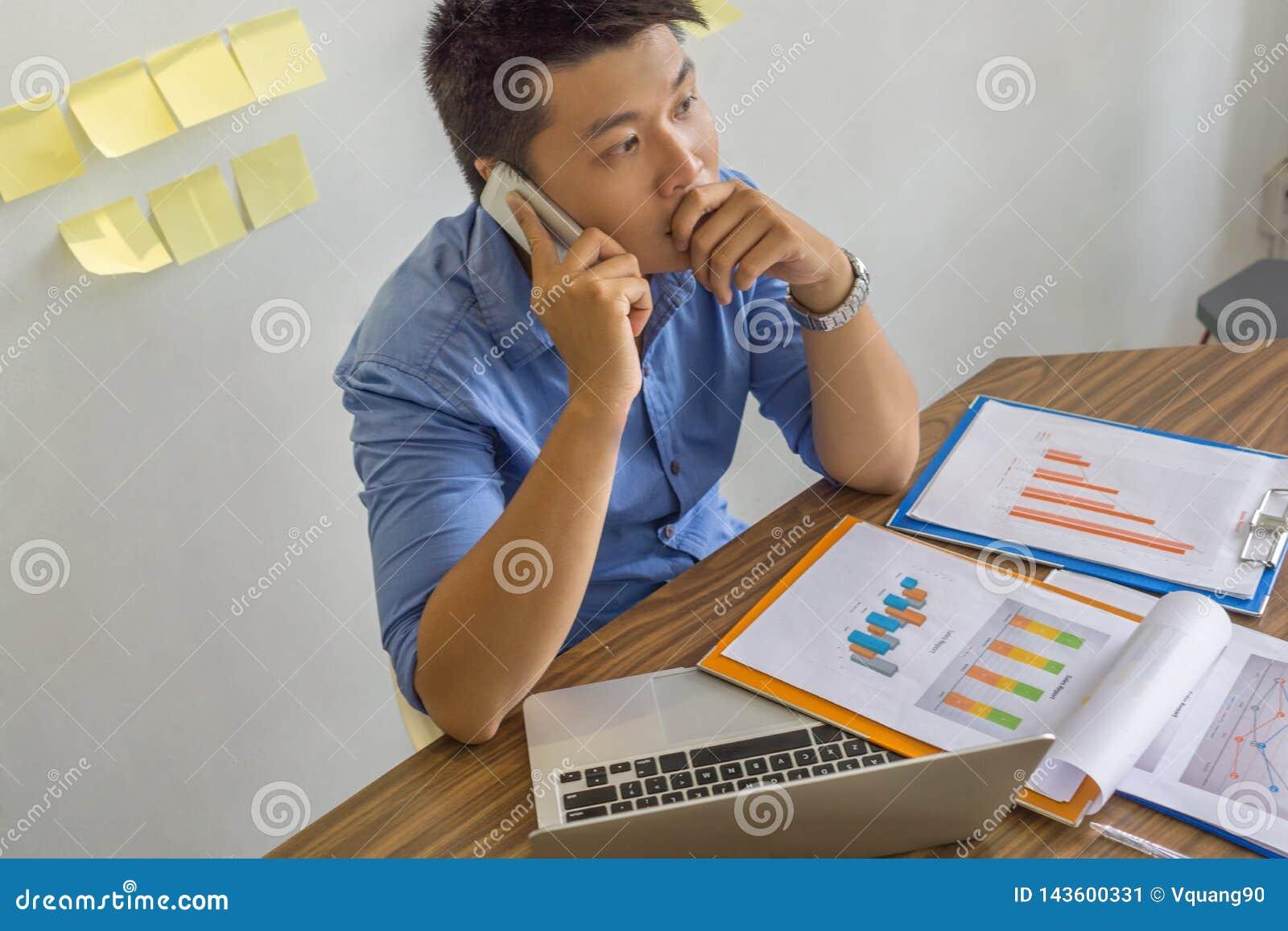 亚洲商人谈话在关于事务的智能手机