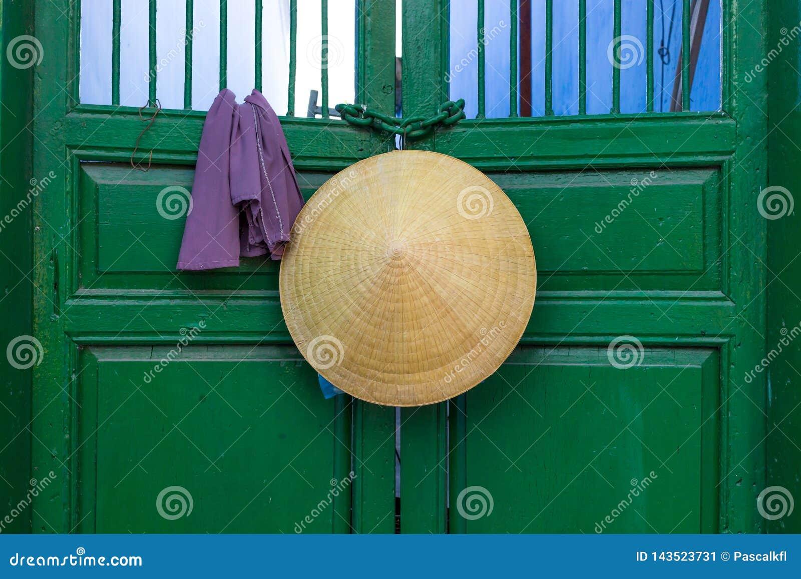亚洲垂悬在一个绿色门的样式圆锥形帽子在越南