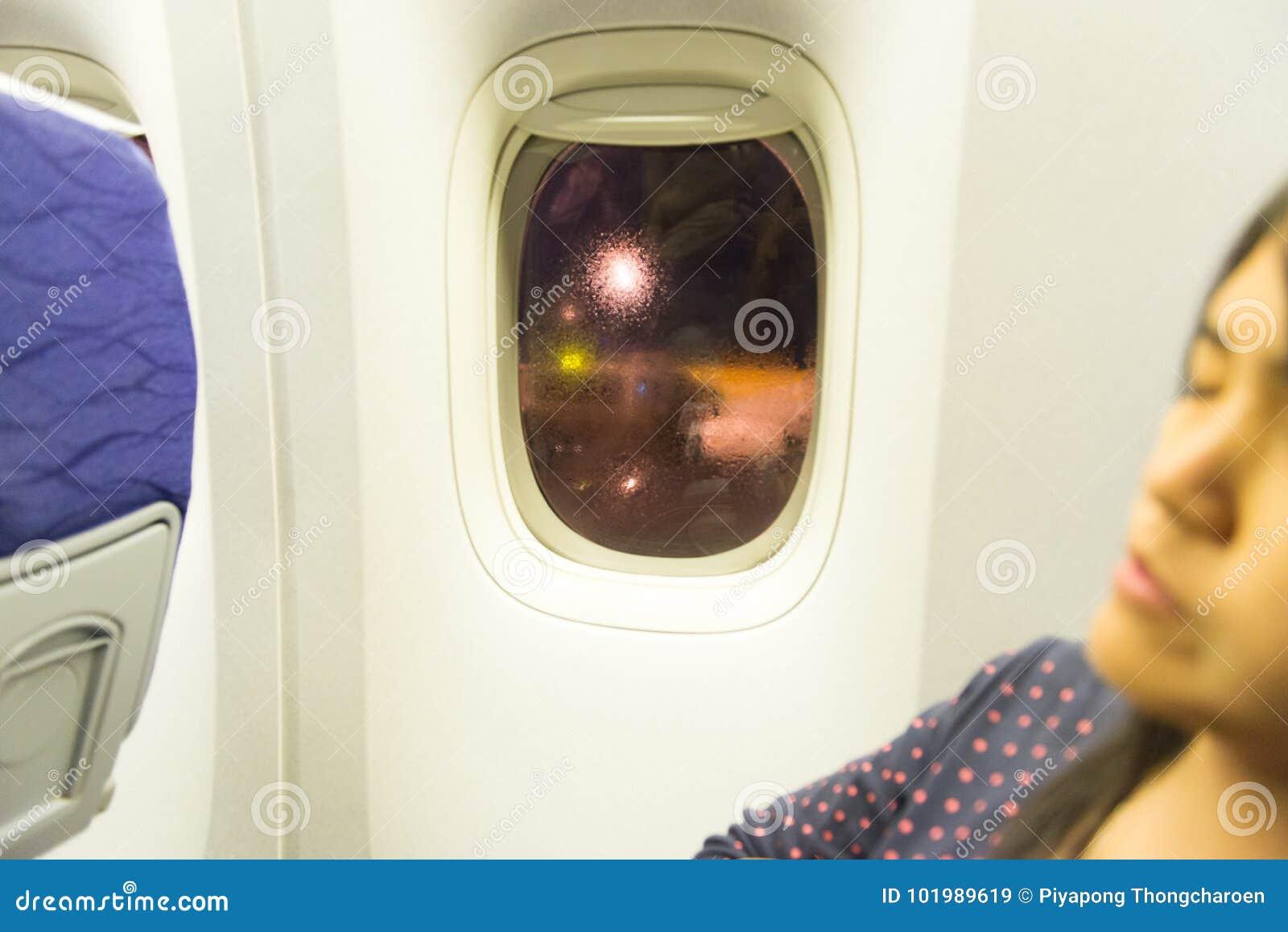 亚洲妇女旅行家睡觉选址在飞机的窗口附近在飞行期间