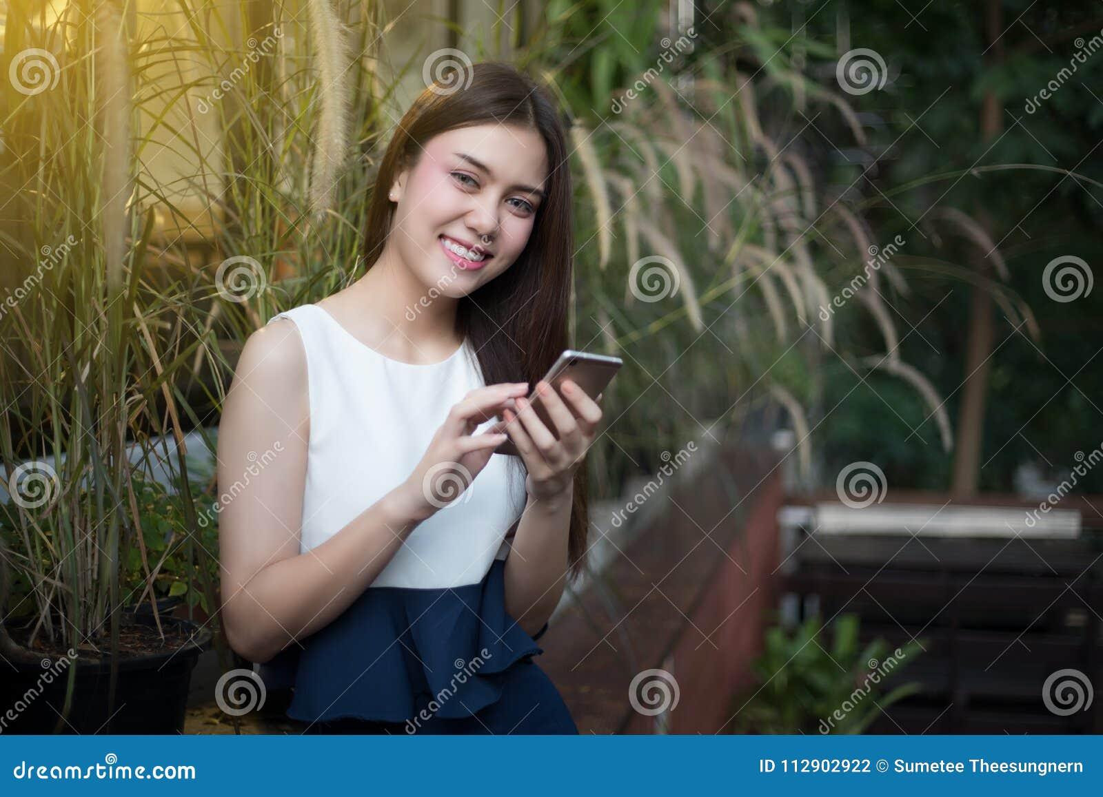 亚洲妇女是微笑和使用机动性并且接触巧妙的电话f
