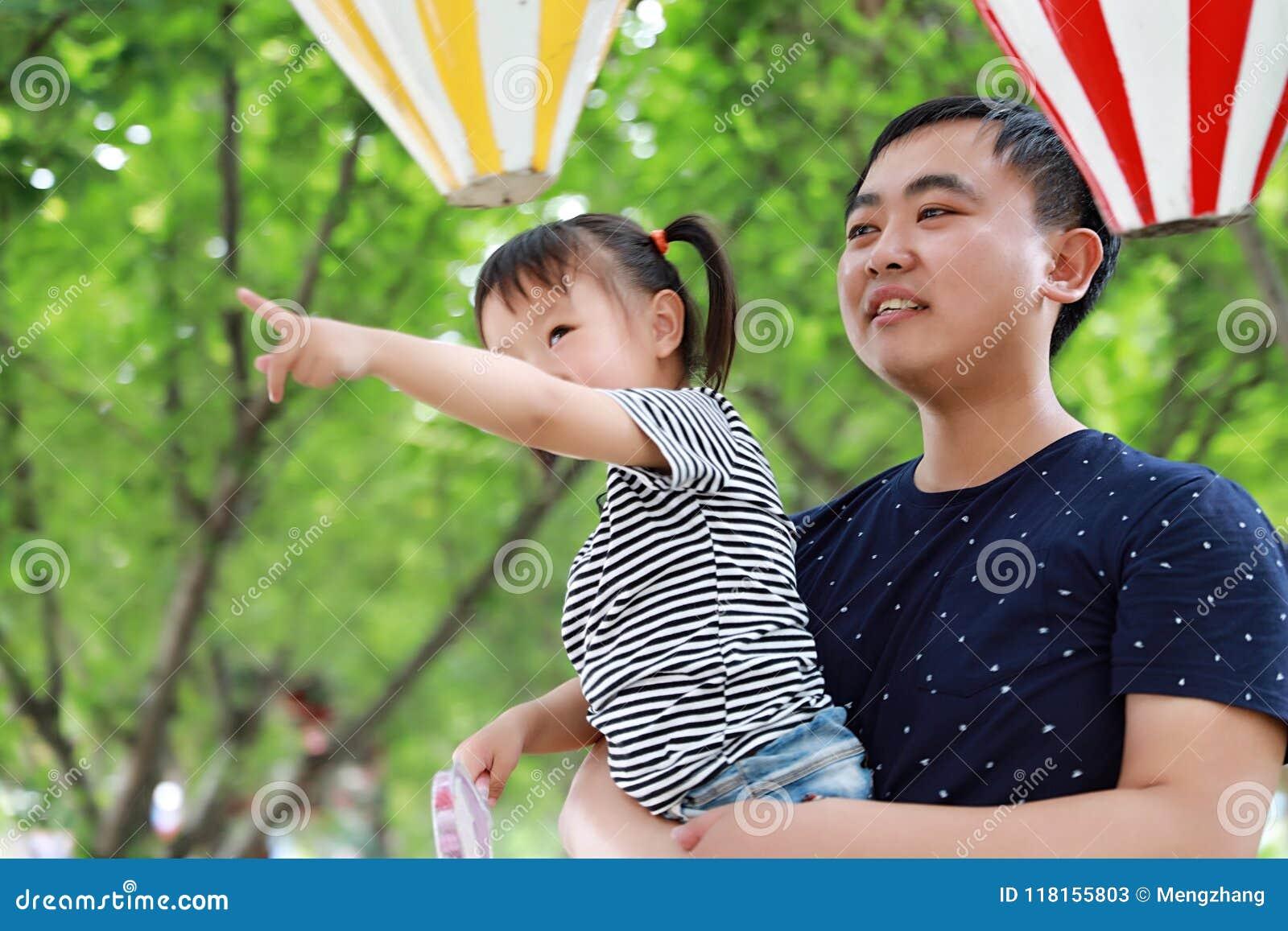 亚洲父亲容忍拥抱女儿爸爸爱女孩儿童游戏获得乐趣在公园室外夏日家庭活动愉快的童年