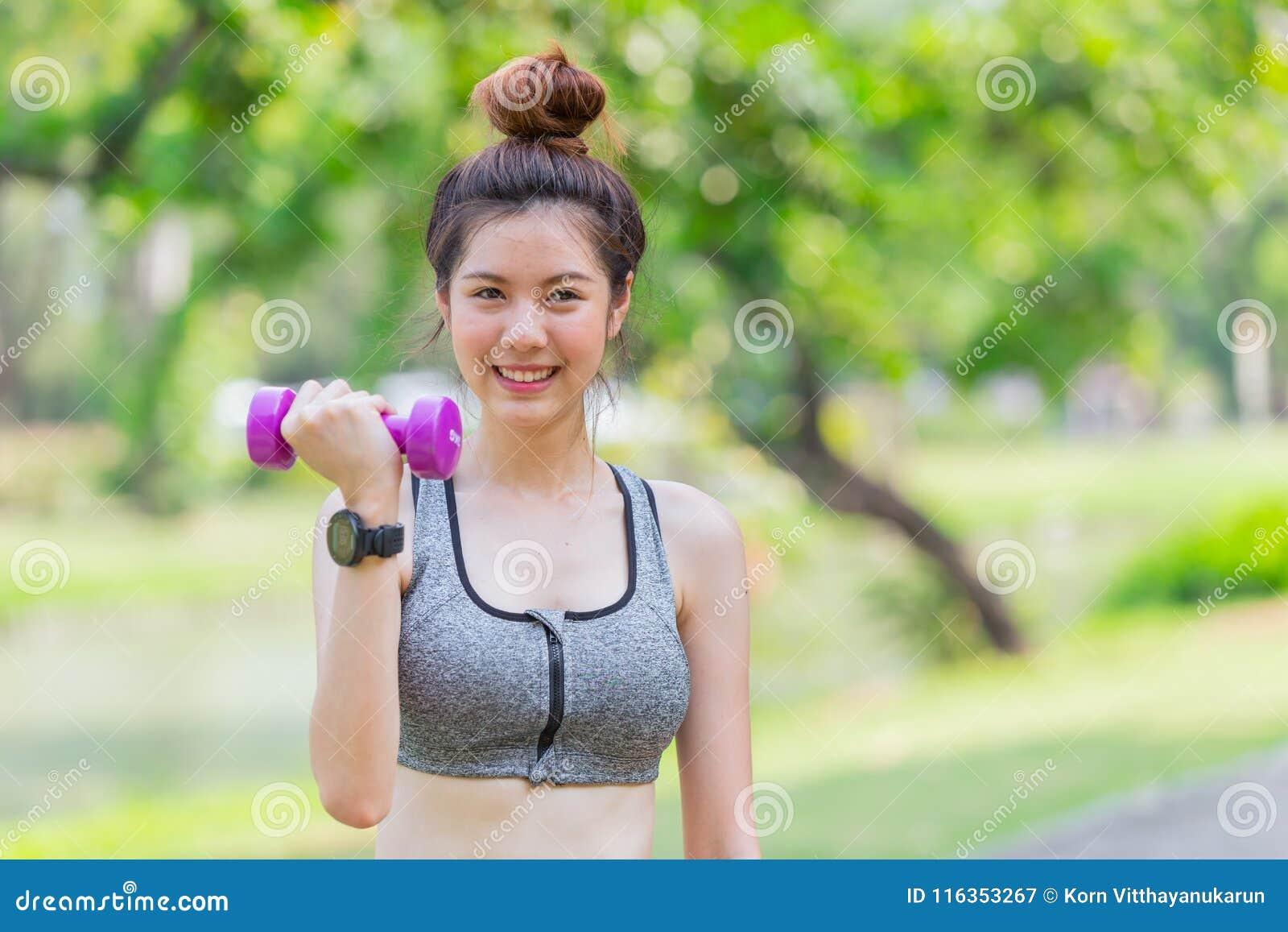 亚洲逗人喜爱青少年亭亭玉立和健康享受与小哑铃的二头肌锻炼