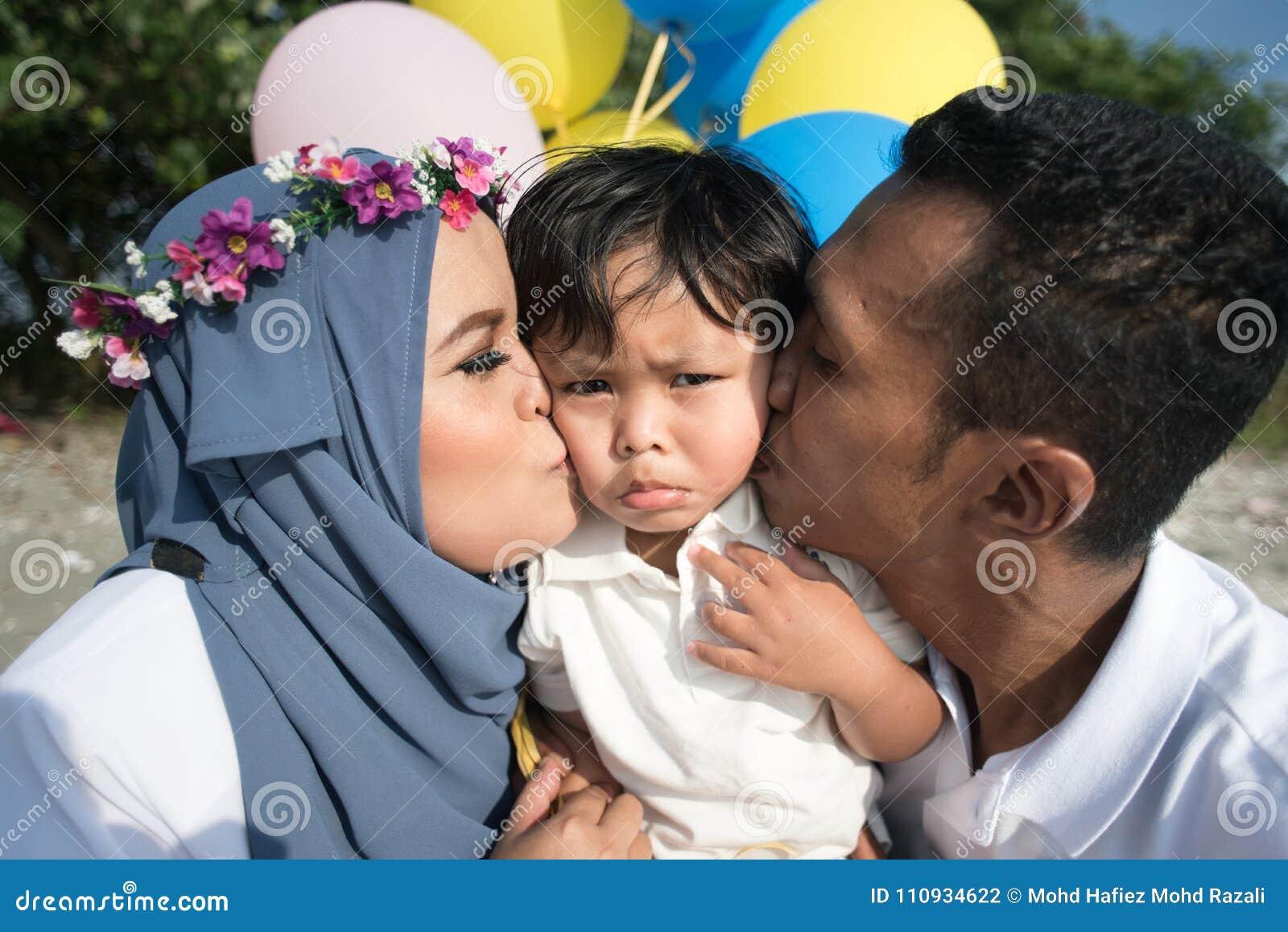 亚裔亲吻他们的儿子的家庭母亲和父亲