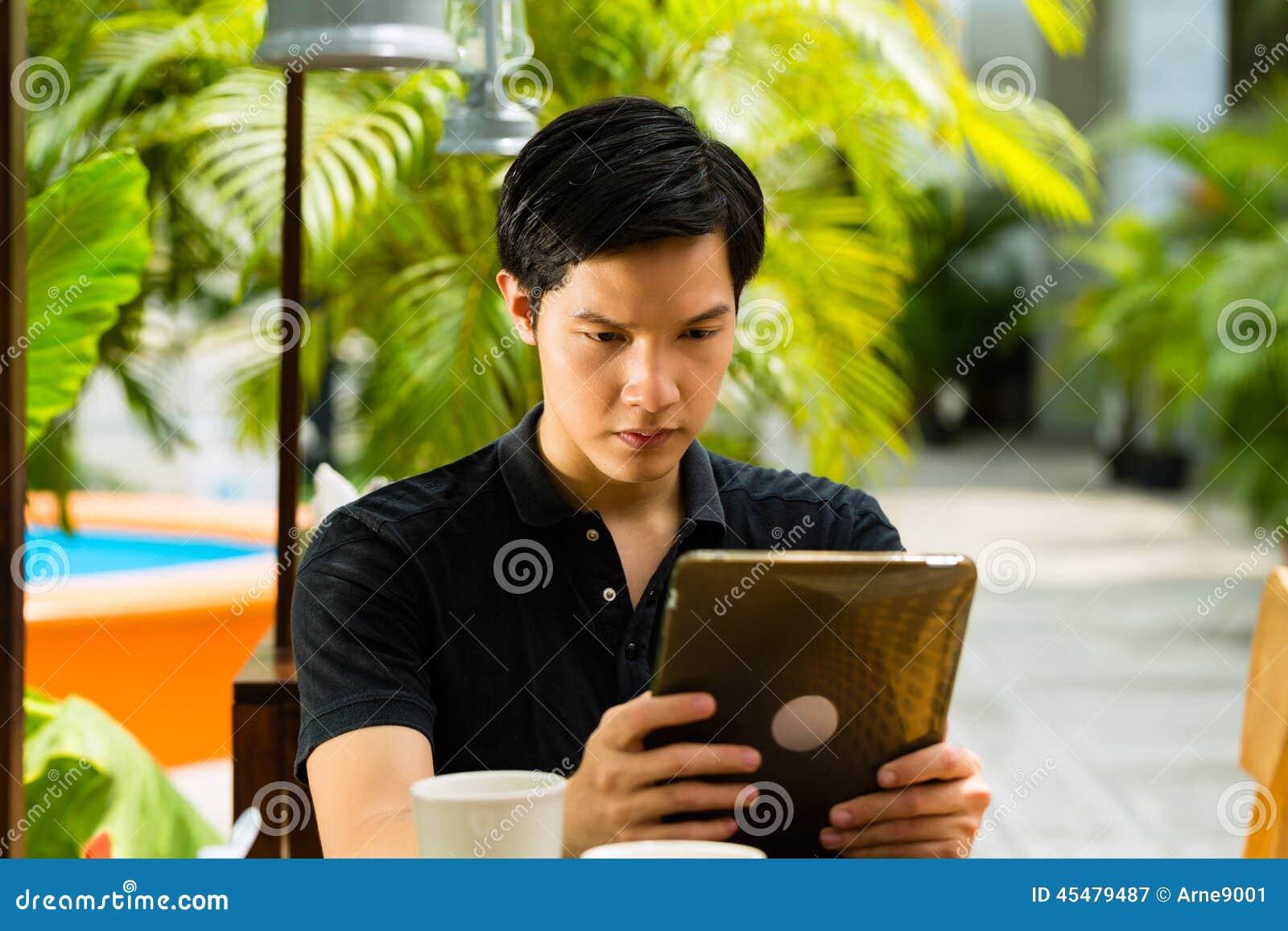 亚裔人在室外的酒吧或的咖啡馆坐