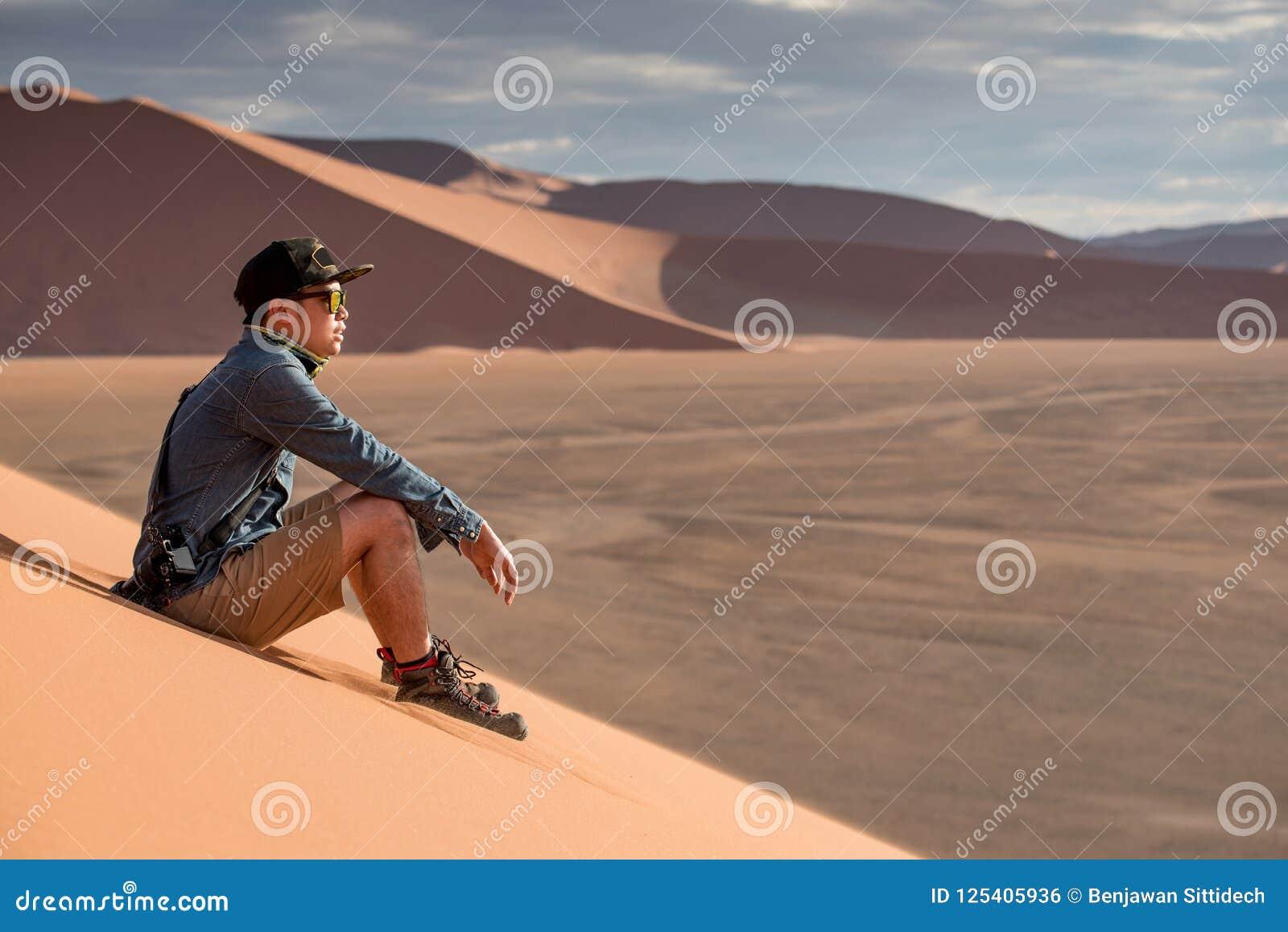 亚裔人摄影师坐沙丘