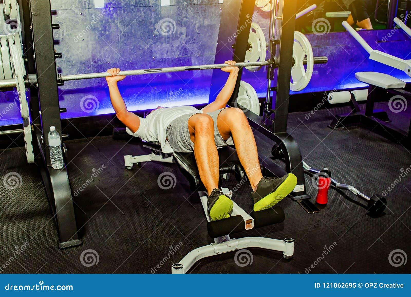 亚裔人行使在卧推人机器生活方式的胸口锻炼健身健康的 隐喻健身和锻炼概念