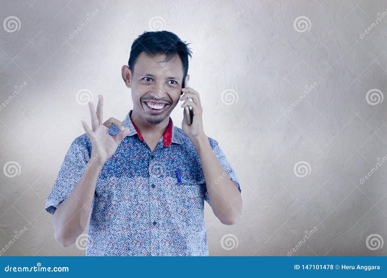 亚裔人谈话在做与手指的被隔绝的灰色背景的电话ok标志,微笑的正面做好标志用手