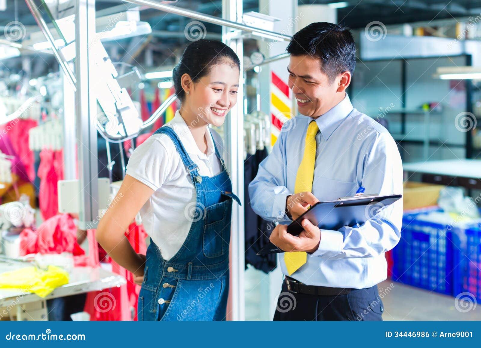 亚裔工头在给训练的纺织品工厂