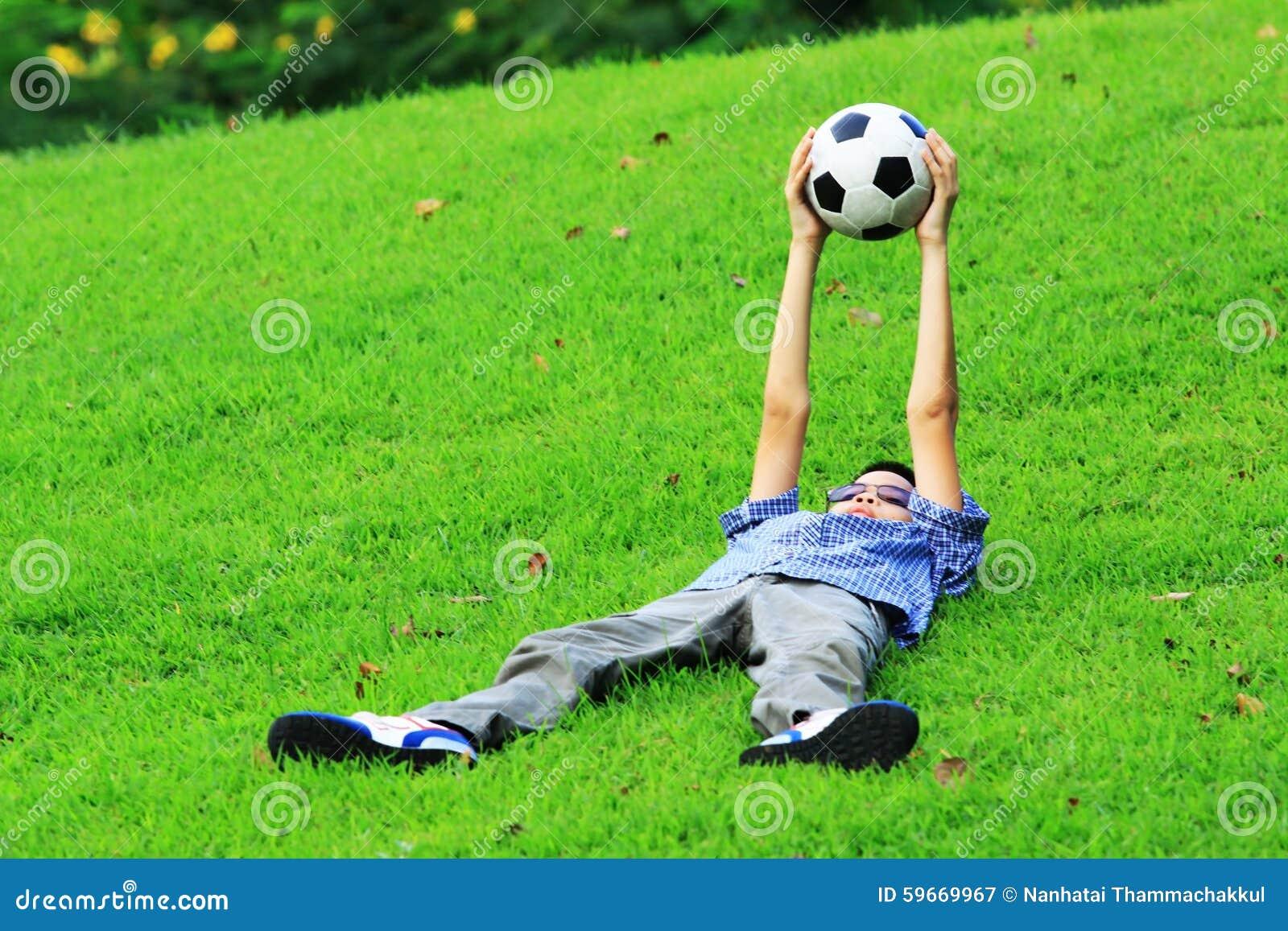 亚裔男孩Portrair在草放下并且举行橄榄球