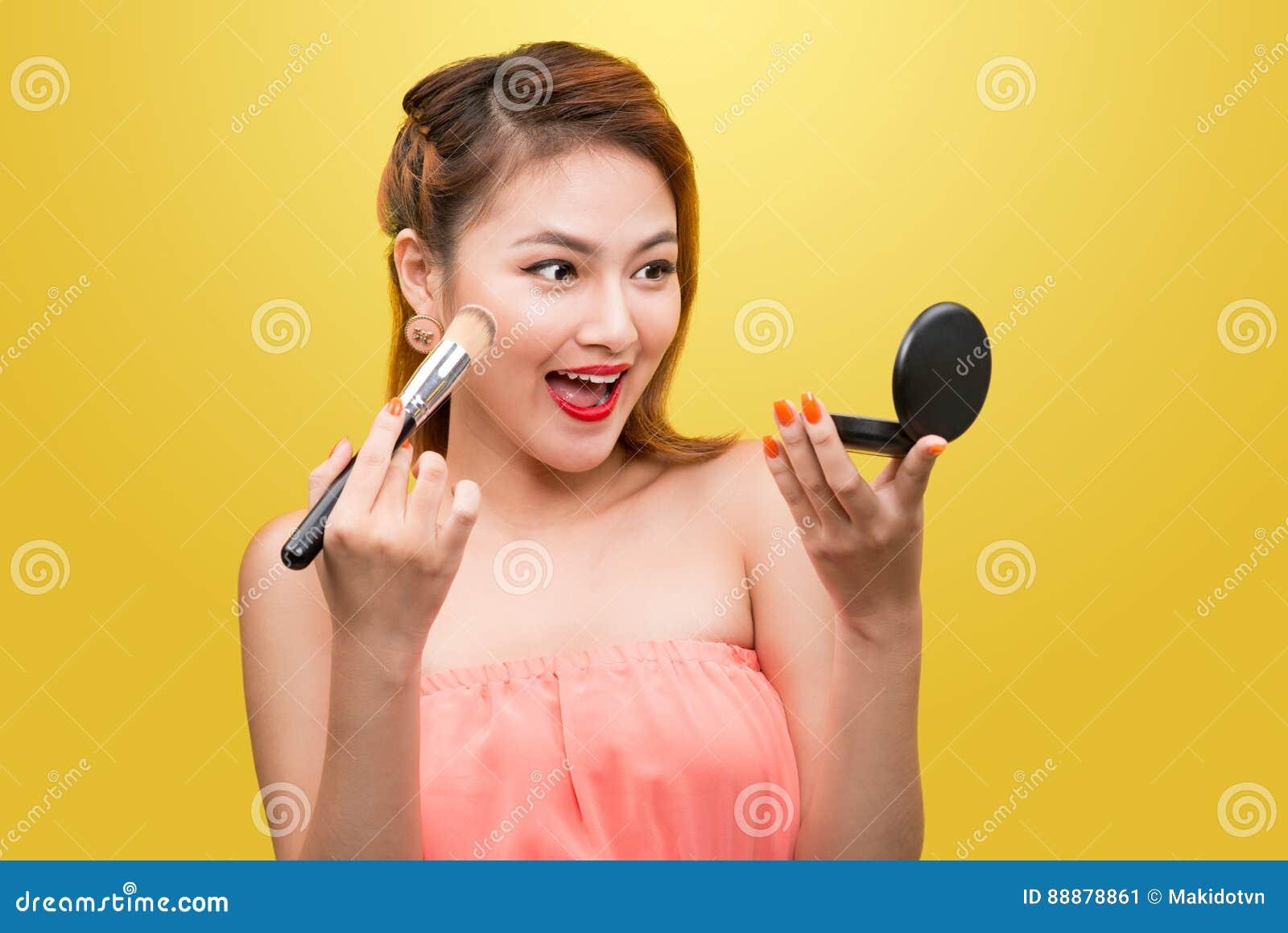 亚裔美丽的妇女画象有构成刷子的在她的fac附近