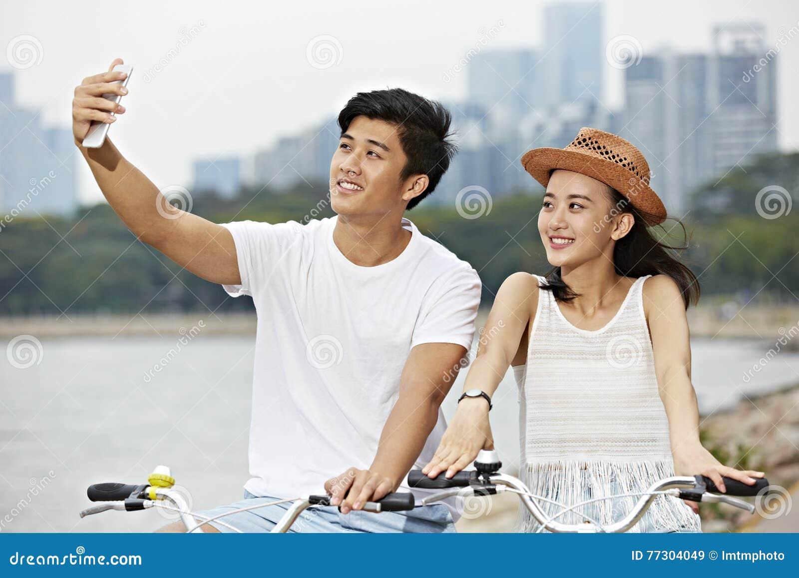 年轻亚洲夫妇骑马自行车和采取selfie