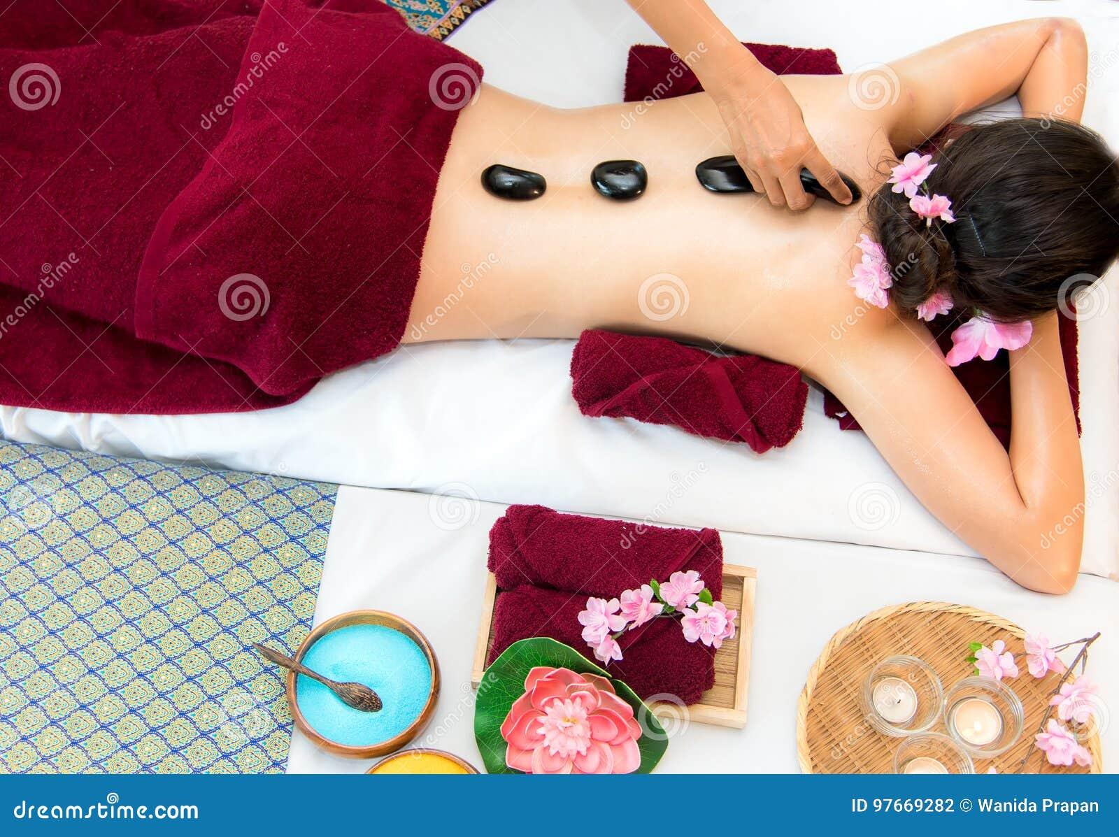 亚洲躺下在与传统热的石头的按摩床上的秀丽妇女沿脊椎在泰国温泉和健康中心,因此放松