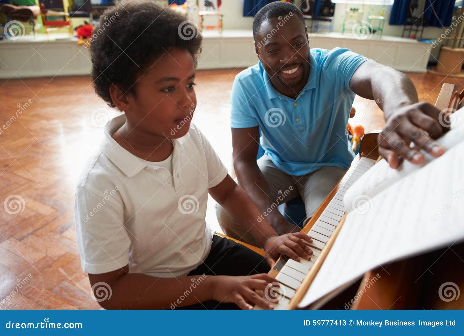 享受与老师的男学生钢琴课