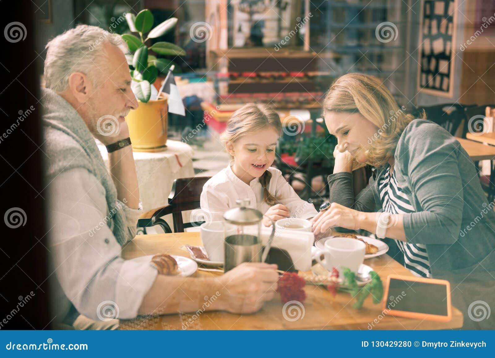 享受他们的与逗人喜爱的聪明的女孩的愉快的祖父母家庭时间