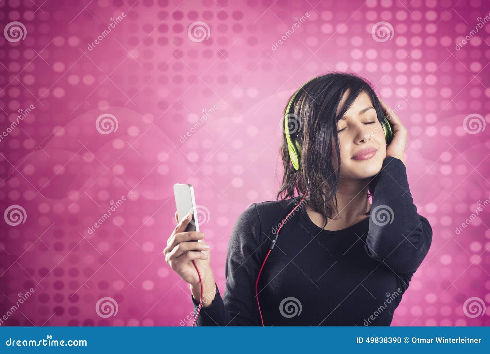 享受听到与耳机的音乐的欢悦镇静女孩