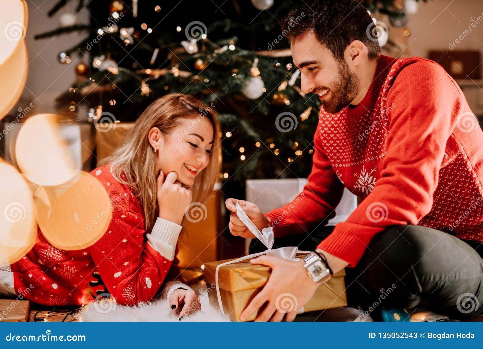 享受圣诞节早晨和打开礼物的夫妇穿配比的毛线衣
