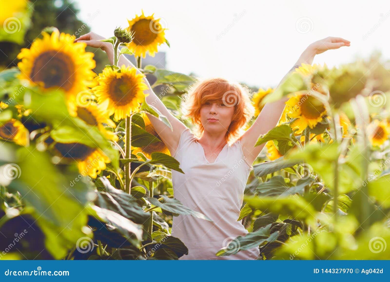 享受在向日葵在日落,美丽的红发妇女女孩的画象的领域的少女自然有的向日葵