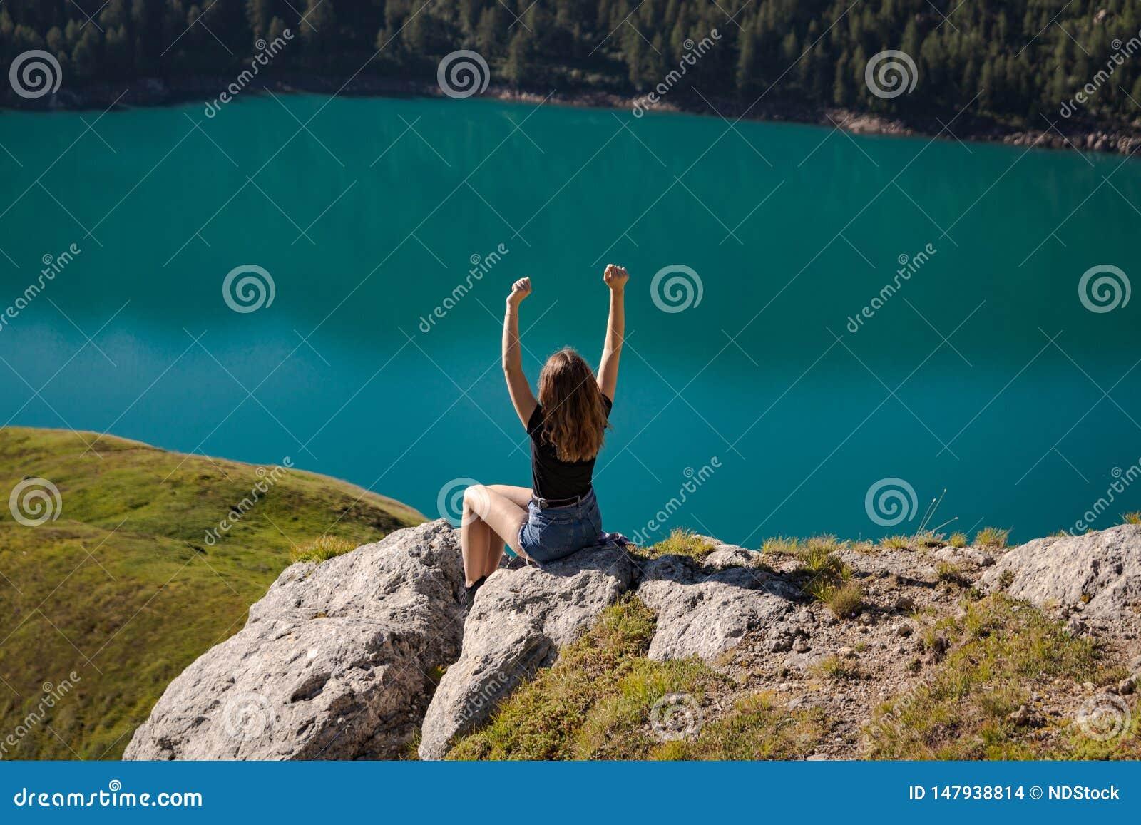 享受在山的上面的正面年轻女人自由与湖ritom的作为背景