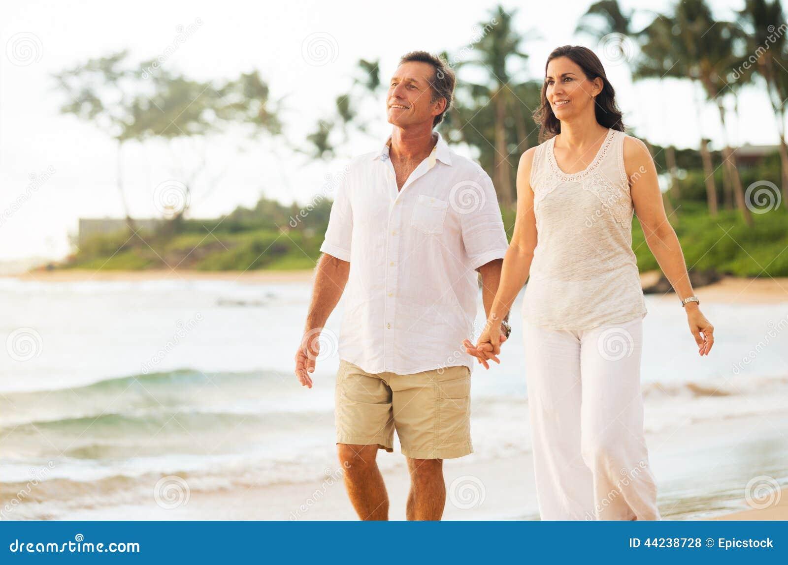 享受在海滩的成熟夫妇步行