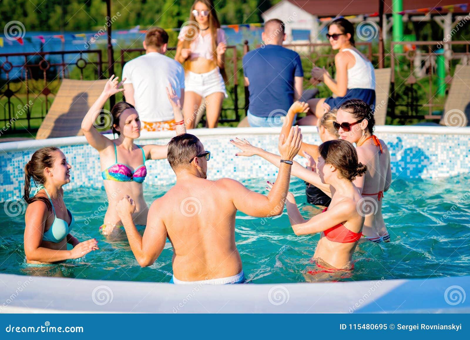 享受在游泳池的愉快的朋友夏令时