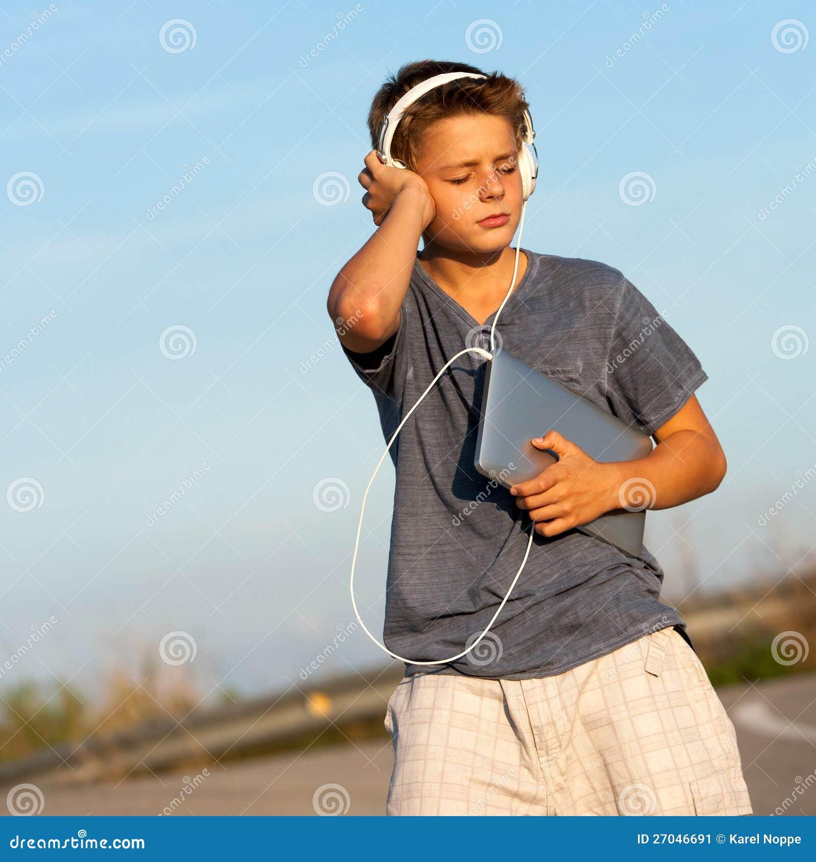 享受在片剂的男孩音乐户外。