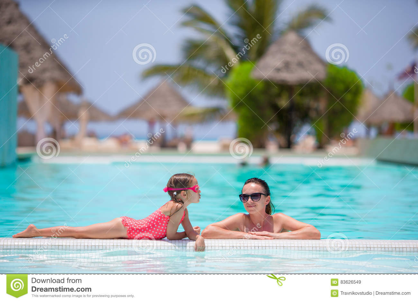 享受在豪华游泳池的母亲和孩子暑假