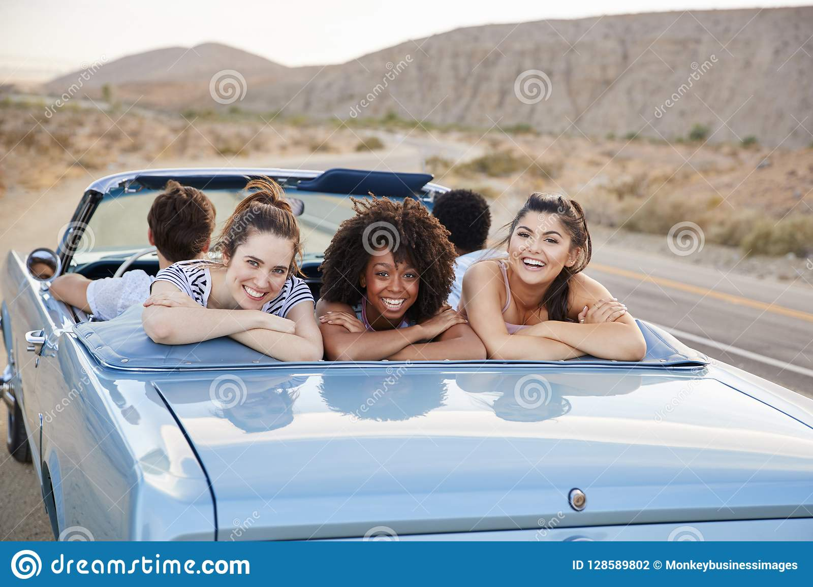 享受在露天经典汽车的三个女性朋友画象旅行