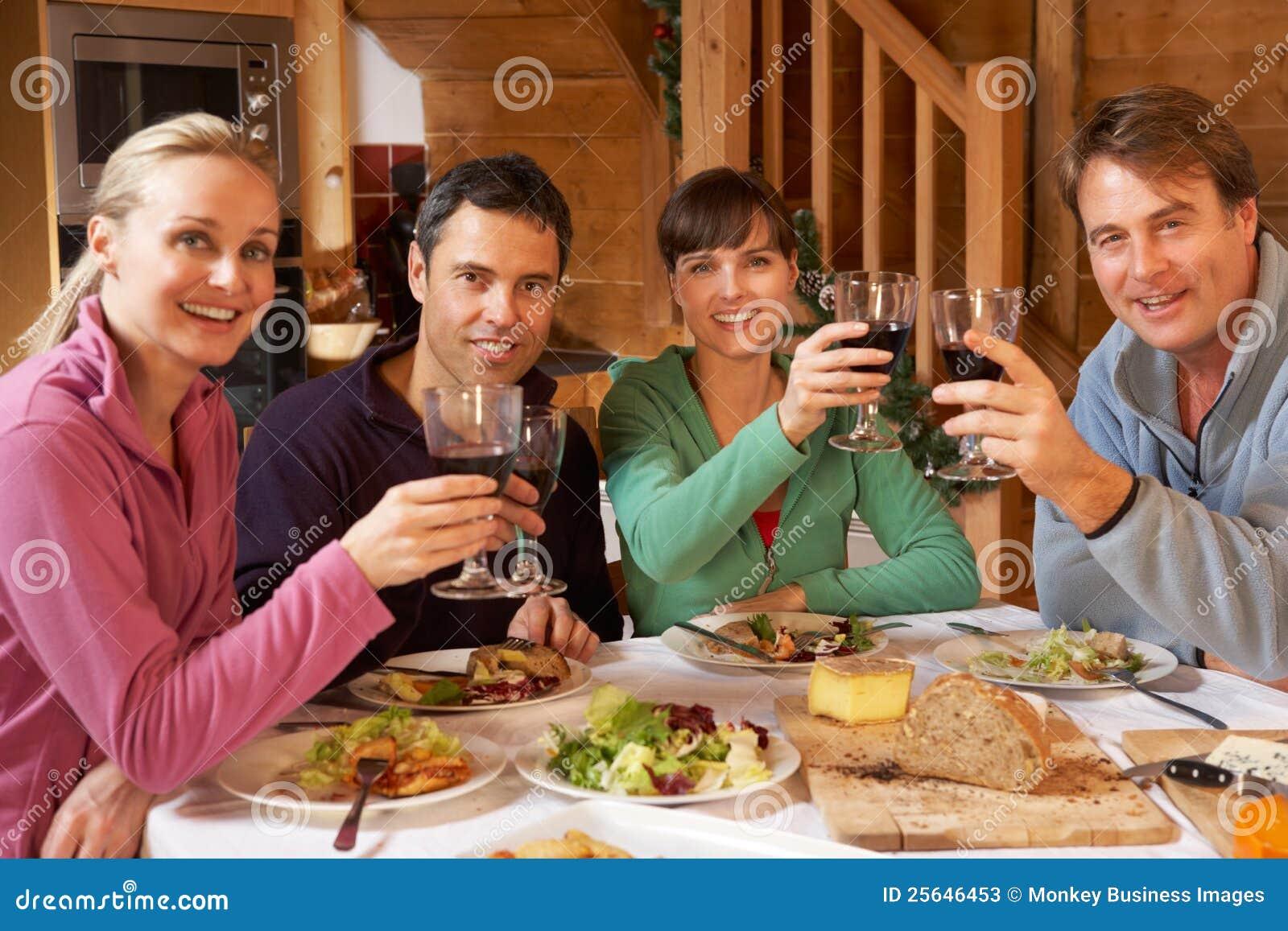 享受在高山瑞士山中的牧人小屋的组朋友膳食
