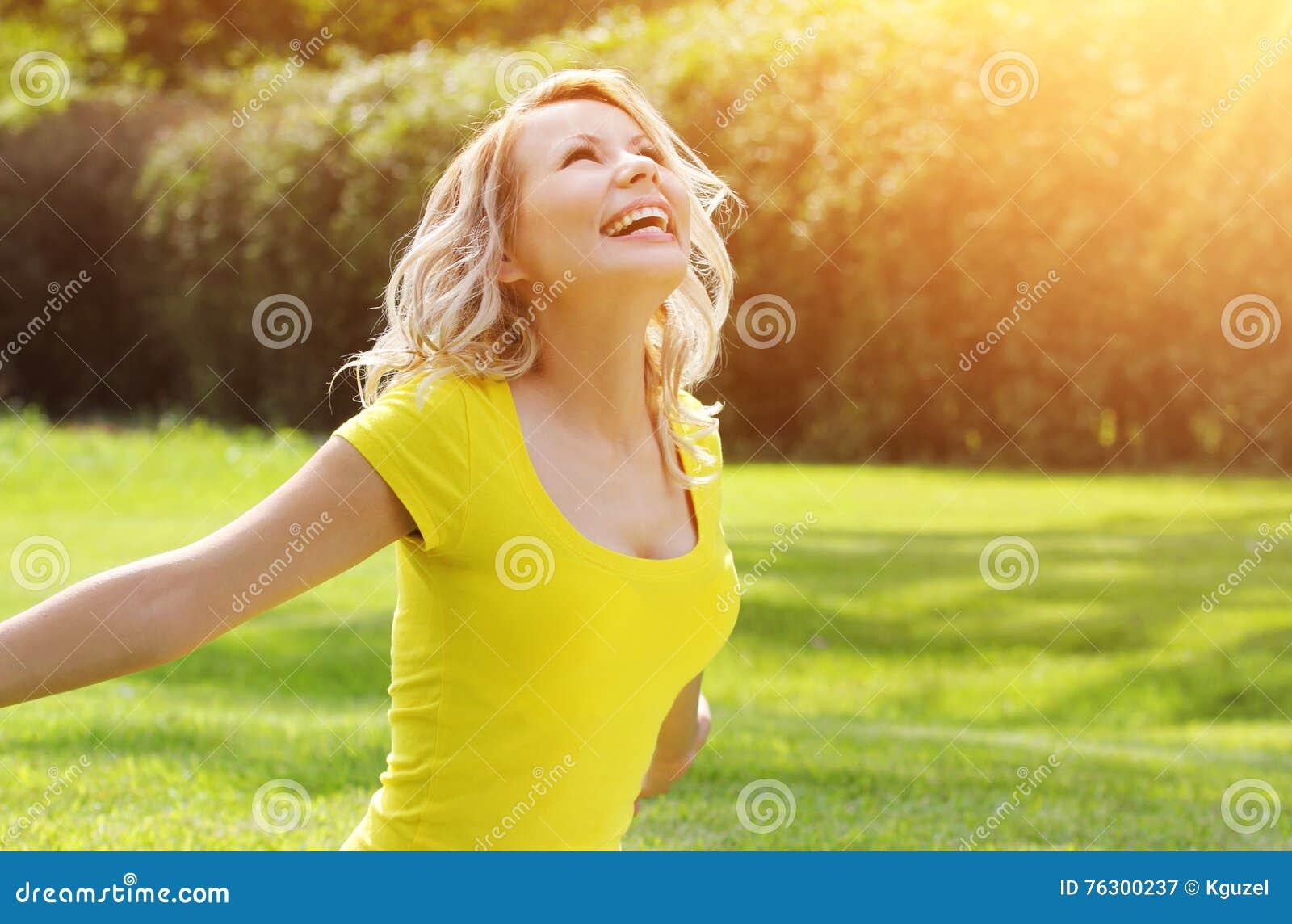 享受在绿草的愉快的女孩自然