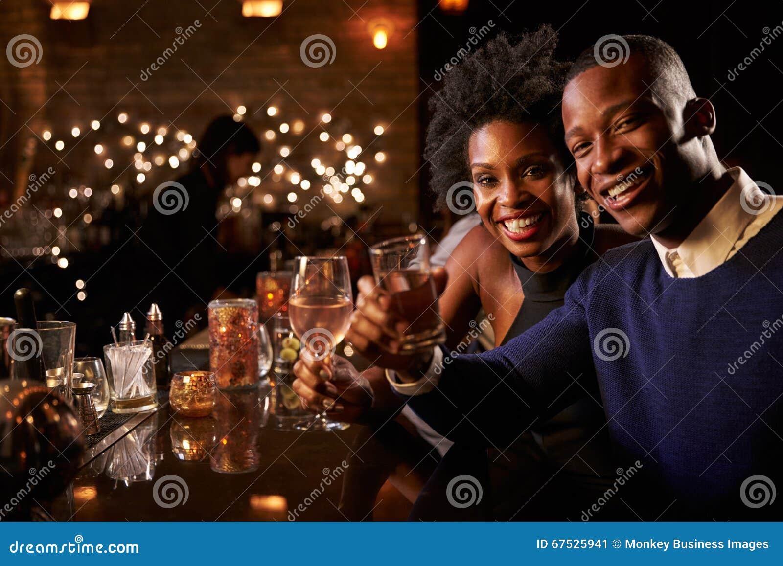 享受夜的夫妇画象在鸡尾酒酒吧