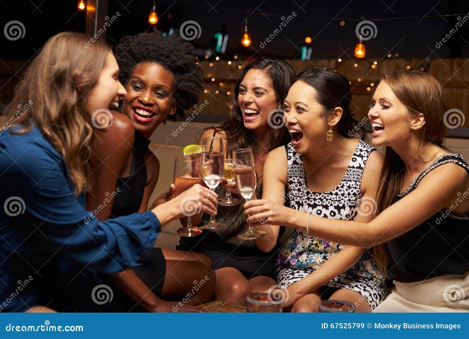 享受夜的小组女性朋友在屋顶酒吧