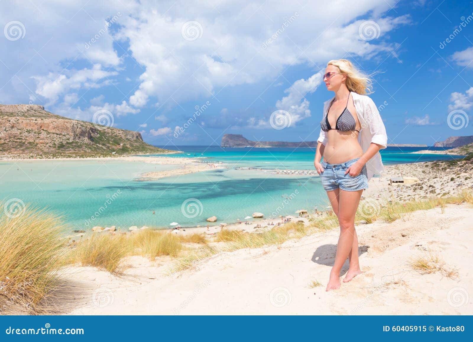 享受太阳的自由的愉快的妇女在度假