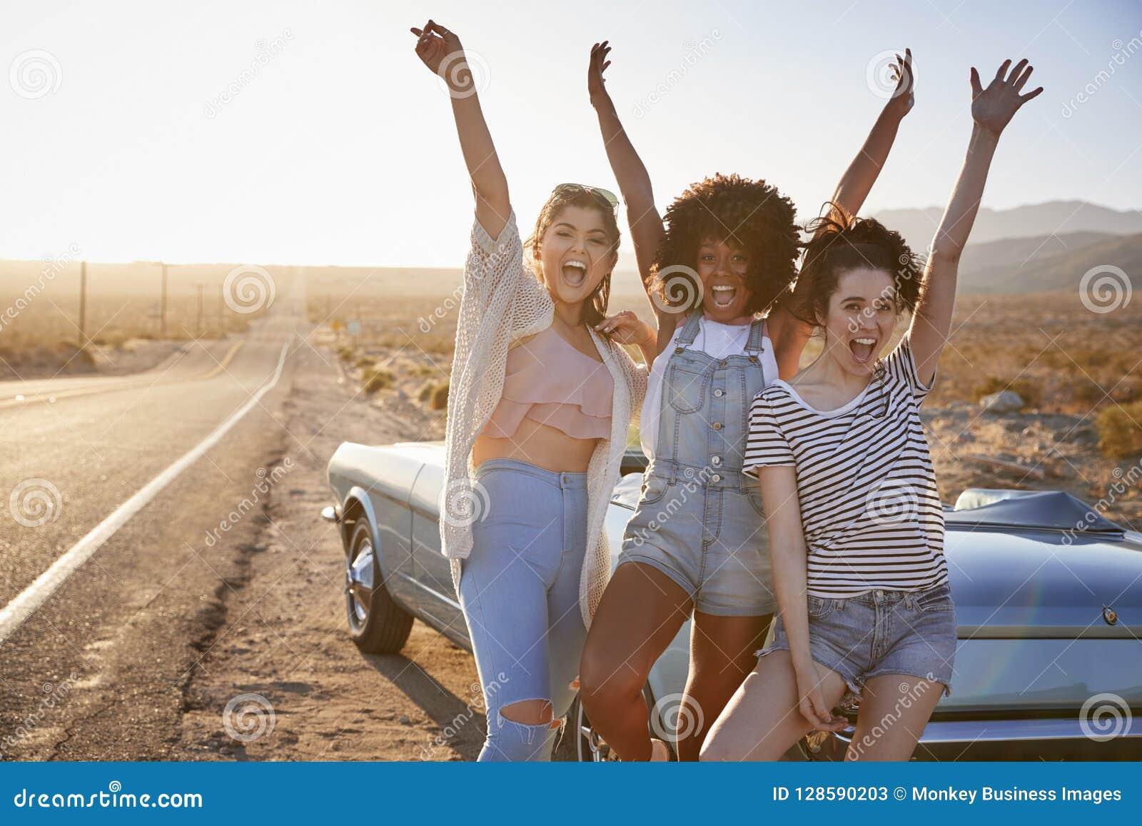 享受旅行的女性朋友画象站立在沙漠高速公路的经典汽车旁边