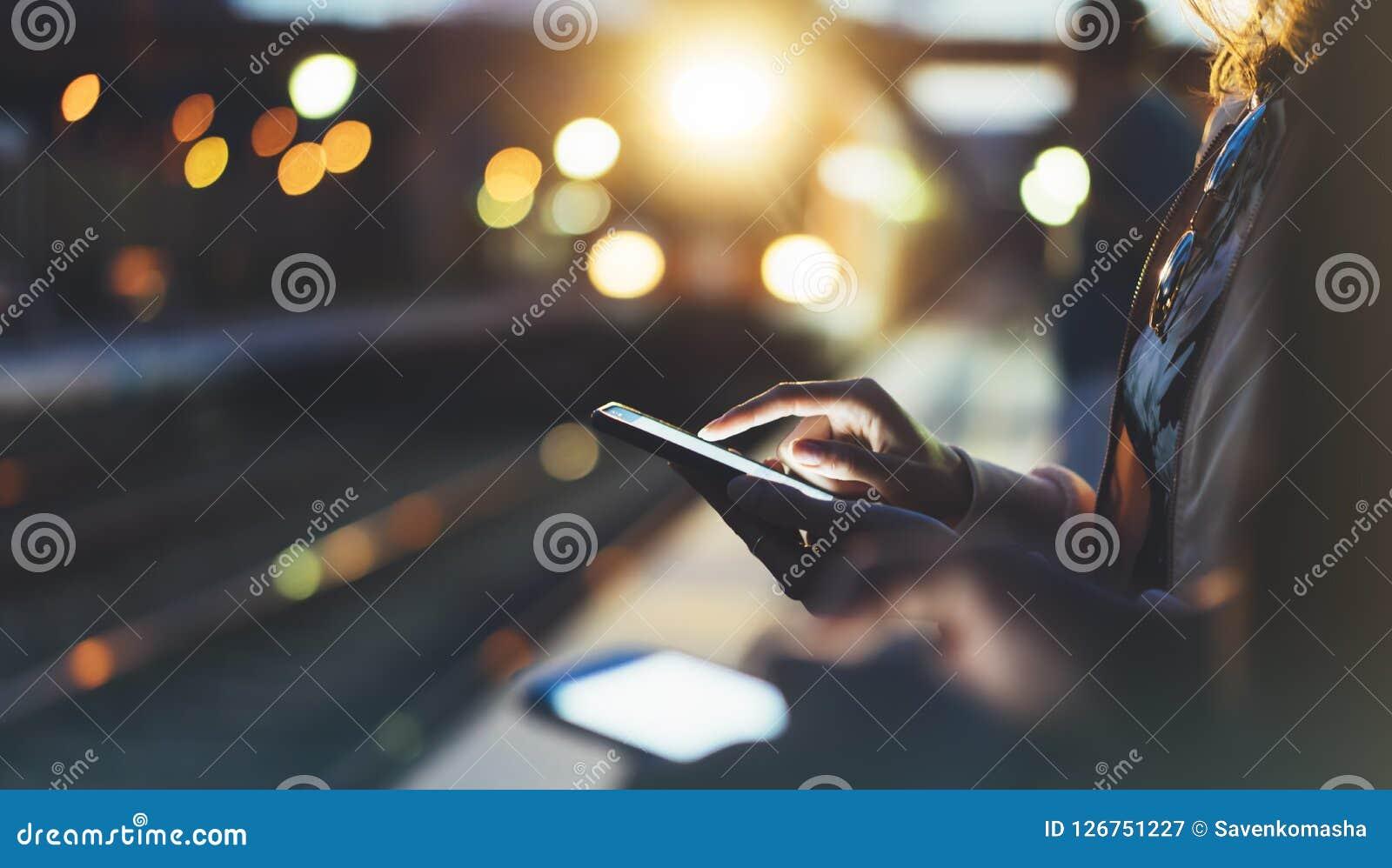 享受旅行 等待在背景光电移动的火车的驻地平台的少妇使用巧妙的电话在夜