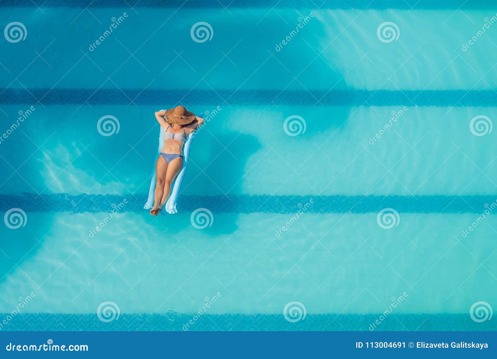 享受晒黑 美丽的概念池假期妇女年轻人 亭亭玉立的少妇顶视图比基尼泳装的在大游泳池的蓝天床垫