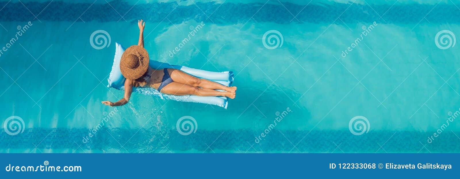 享受晒黑 美丽的概念池假期妇女年轻人 亭亭玉立的少妇顶视图比基尼泳装的在大游泳池横幅的蓝天床垫