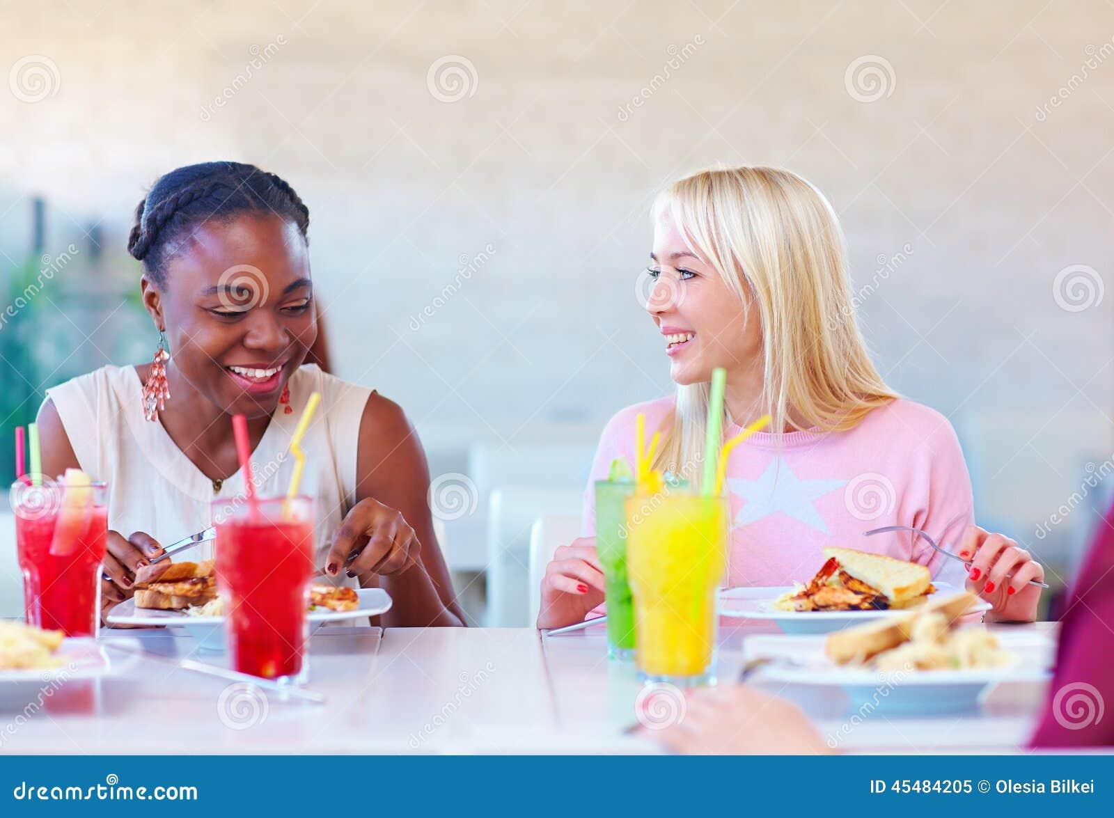 享受膳食的多种族女性朋友在餐馆