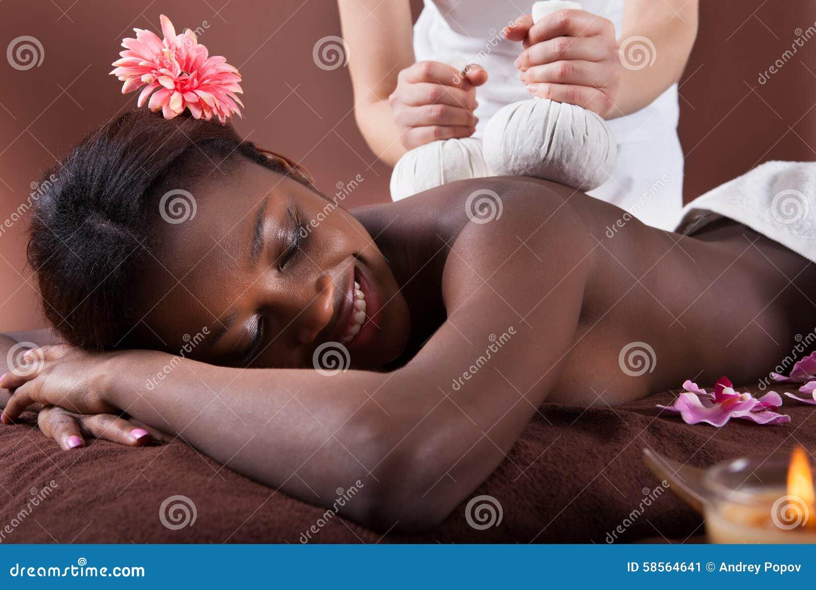 享受草本按摩的妇女在温泉