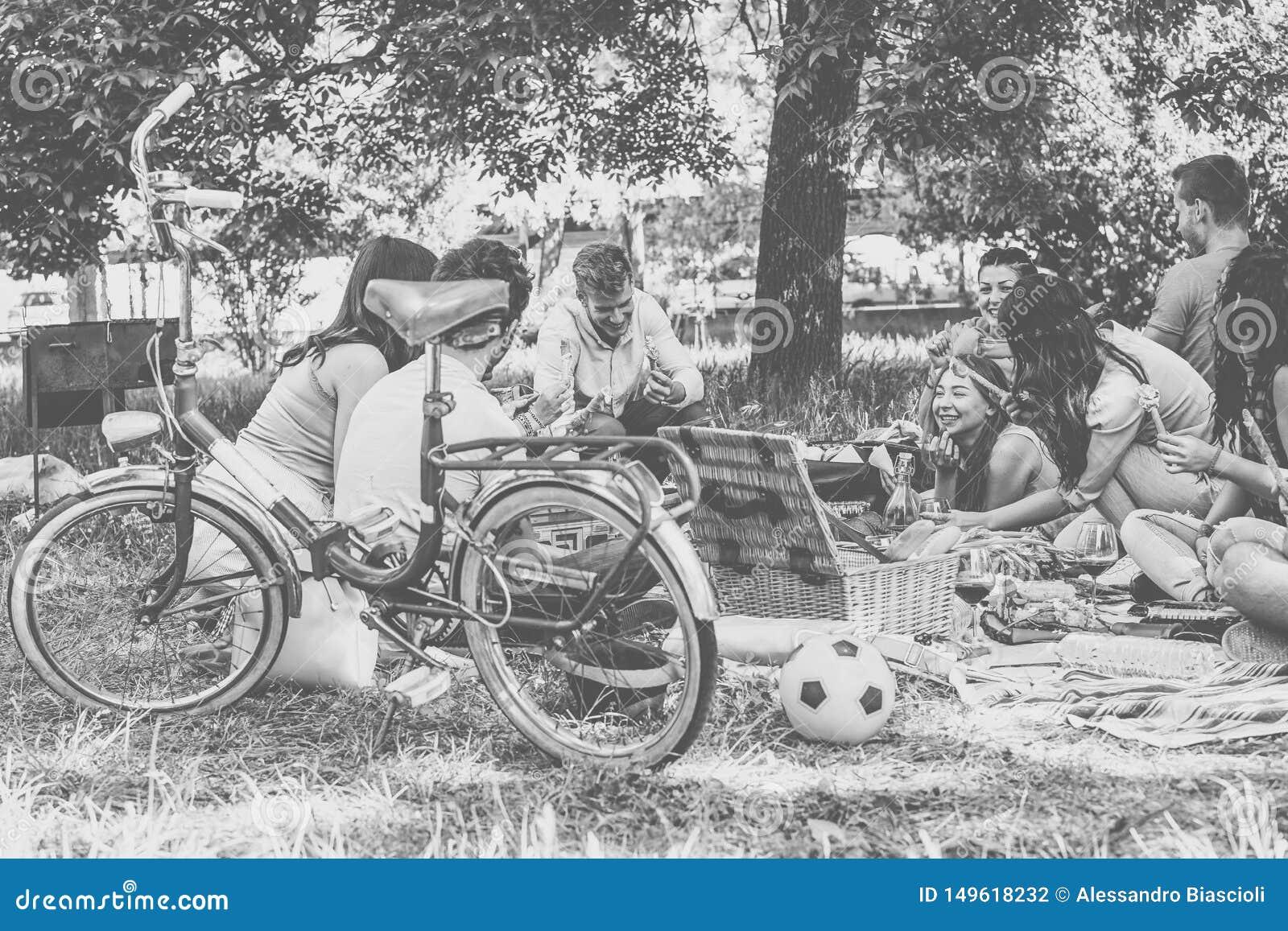 享受野餐的小组朋友,当一起时吃和喝红酒在乡下-获得愉快的人民乐趣