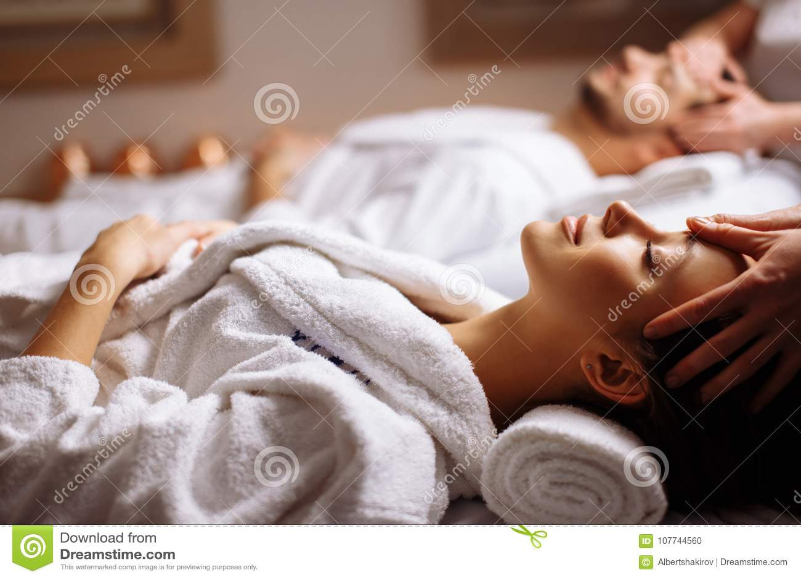 享受顶头按摩的愉快的年轻美好的夫妇在温泉