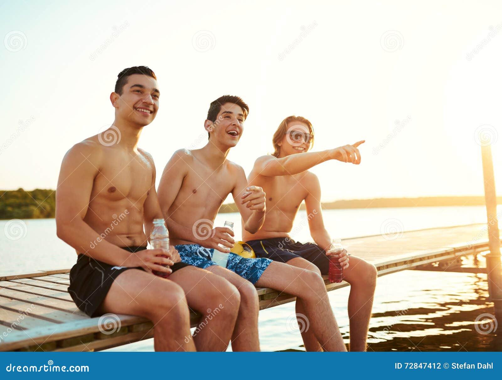 享受饮料的三个男性朋友在日落