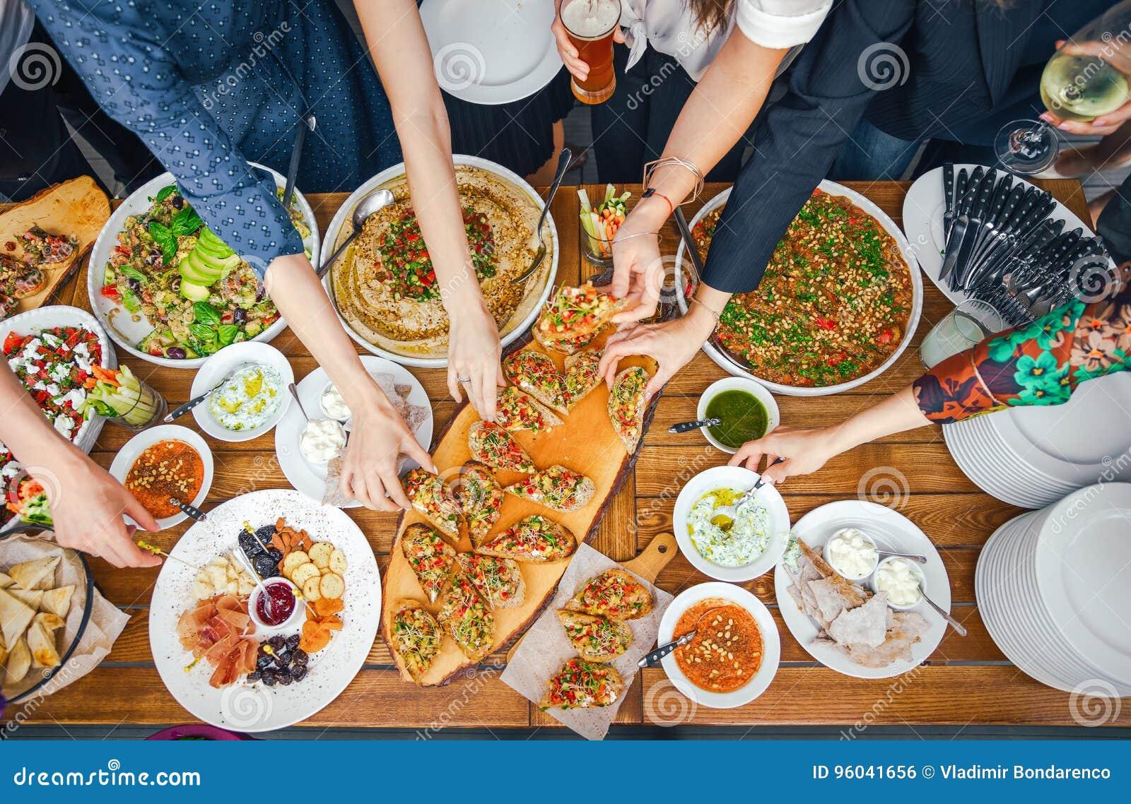 享受Dinning吃概念的朋友幸福 食物自助餐 承办的用餐 吃党 共享概念